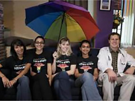 MedPride members posing for photo holding rainbow umbrella