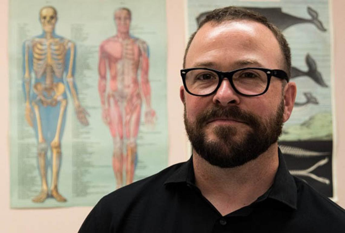Portrait of Eric with a human anatomy chart in the background
