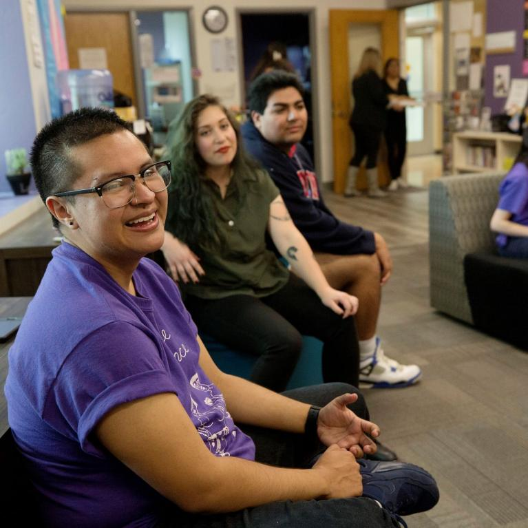 Members of LGBTQ sitting in common area smiling for a photo