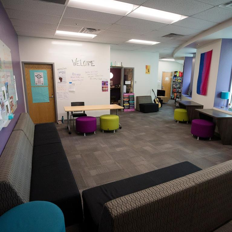 Common area filled with couches and colorful stools