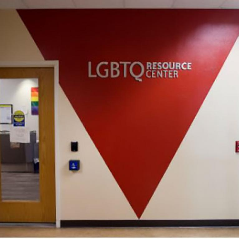 "Hallway wall with ""LGBTQ Resource Center"" painted inside a red triangle"