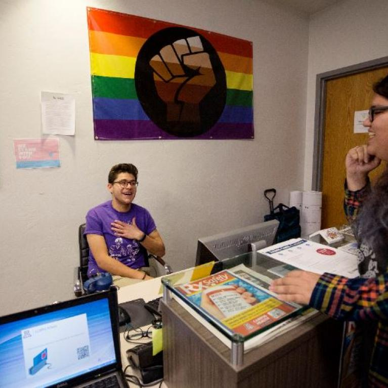 Two members of LGBTQ conversing at a desk, a pride flag hanging behind them on the wall